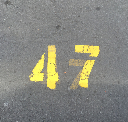 Photo of a number forty-seven or 47 spray painted in yellow color on asphalt road in Auckland, New Zealand. Stock Photo