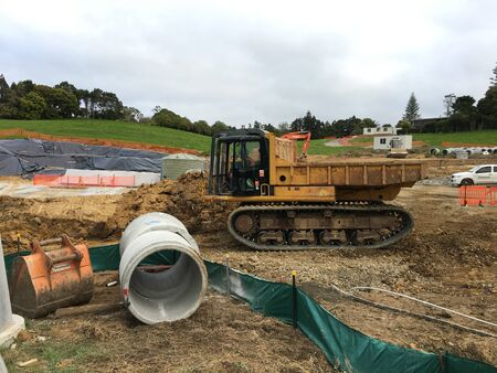 AUCKLAND, OCT. 4: A dump truck on tracks operation by clearing the ground foundation in a building construction site in Auckland, New Zealand taken on Oct. 4, 2017. Zdjęcie Seryjne - 137101192