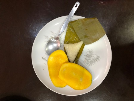 Photo of slices of Philippine mango fruit and suman, a  Filipino rice cake  made from glutinous rice cooked in coconut milk, often wrapped in banana leaves on a plate.