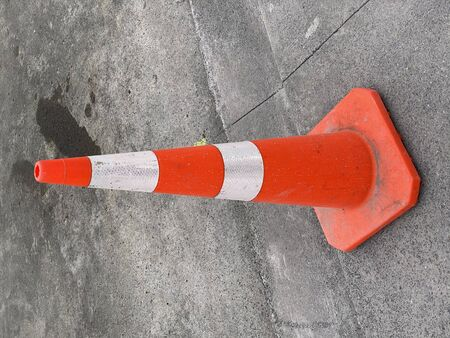 Photo of a traffic cone or road cone on asphalt road.
