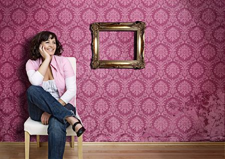 girl sitting on a chair in front of a pink 70s wallpaper Stock Photo - 5215002