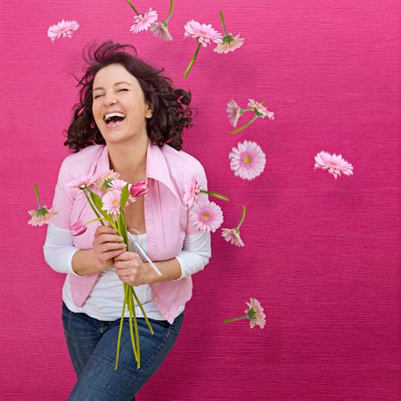 laughing girl in front of a pink wall, flowers falling down photo