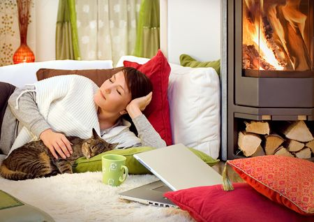 woman with a little cat is sleeping beside a fireplace photo