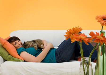 lay: young woman sleeping on a sofa with a little cat