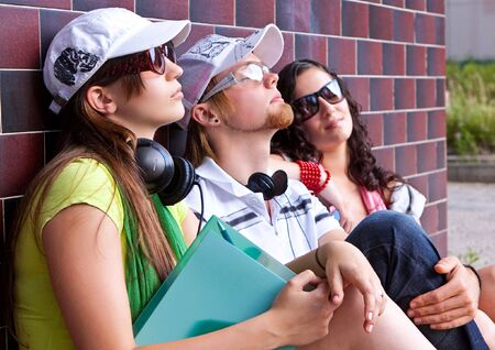 students are sitting beside a wall and making a rest Stock Photo - 5437855