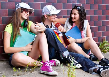 students are sitting beside a wall and making a rest Stock Photo - 5437825
