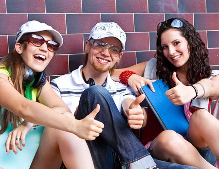 students are sitting beside a wall and making a rest Stock Photo - 5437858
