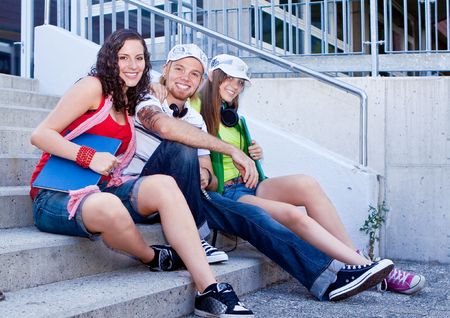 students sitting on the stairs of a schoolyard photo
