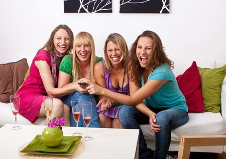friends laughing: pretty girls looking tv and making a little party