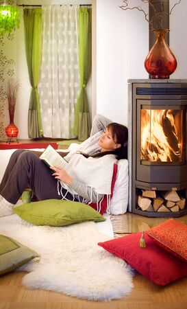 wood stove: woman with a book relaxing in front of a fireplace