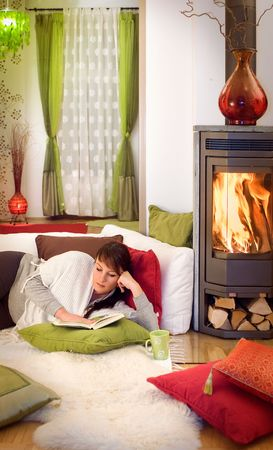 woman with a book relaxing in front of a fireplace