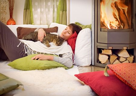 cuddles: woman with a little cat relaxing in front of a fireplace