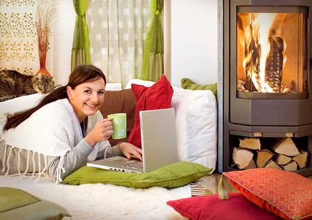 woman with a little cat relaxing in front of a fireplace photo