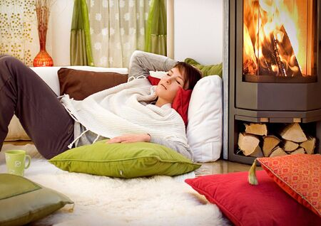 woman relaxing in front of a fireplace Stock Photo - 5512259