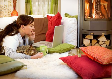 woman with a little cat relaxing in front of a fireplace