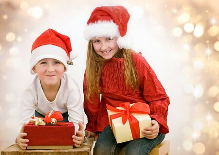 golden  gleam: children with gifts at christmas Stock Photo