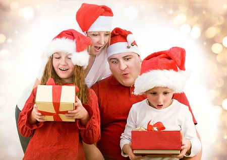 golden  gleam: young family with gifts at christmas Stock Photo