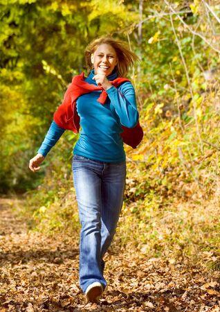 power walking: girl taking a walk in an autumn-forest