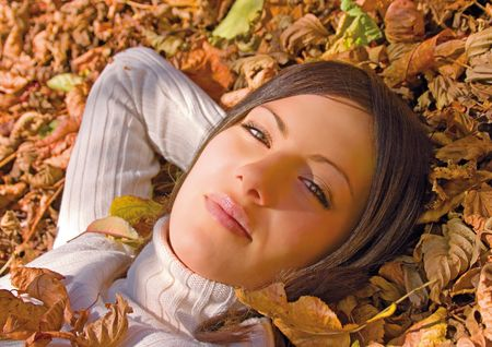 pretty girl lying in autumn-leaves photo