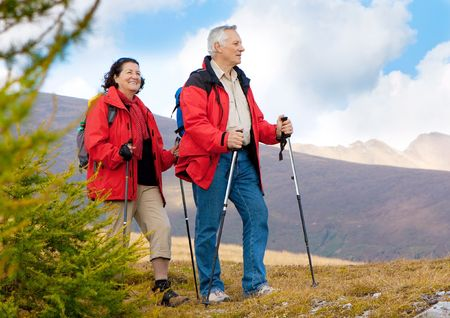 nordic walking: cute seniorcouple hiking in an autumn mountainlandscape Stock Photo