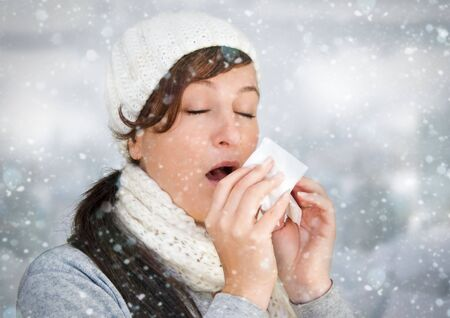 woman with a cold holding a tissue - its snowing photo