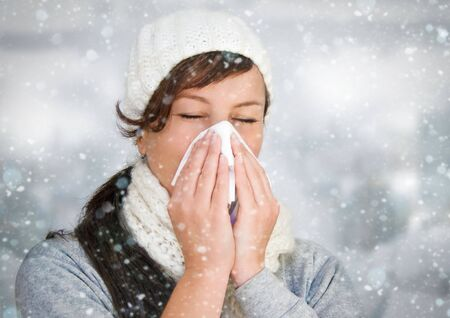 woman with a cold holding a tissue - its snowing Stock Photo