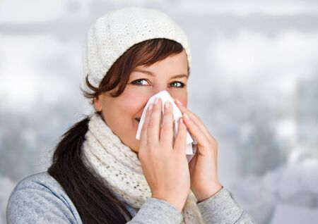 woman with a cold holding a tissue (without snow in background) photo