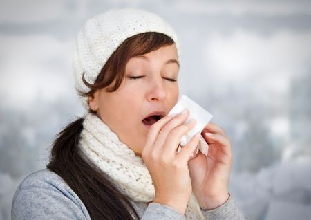 cold virus: woman with a cold holding a tissue (without snow in background)