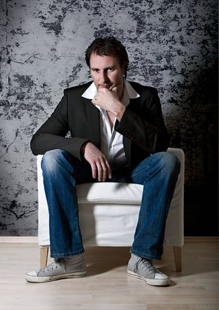 smart man sitting on an armchair photo