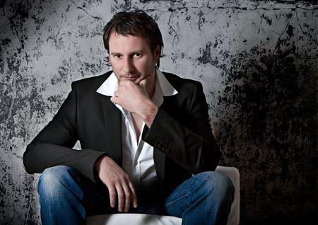 waiting glance: smart man sitting on an armchair Stock Photo