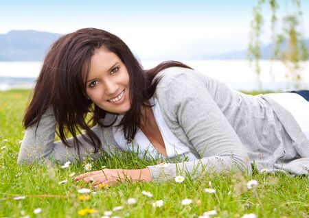 young woman lying in a meadow in front of a lake Stock Photo - 7317160
