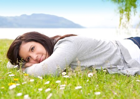 young woman laying in a meadow in front of a lake Stock Photo - 7317171