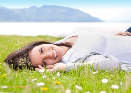 young woman laying in a meadow in front of a lake
