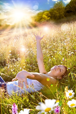 beautiful young girl lying in a sunset marguerite meadow Stock Photo