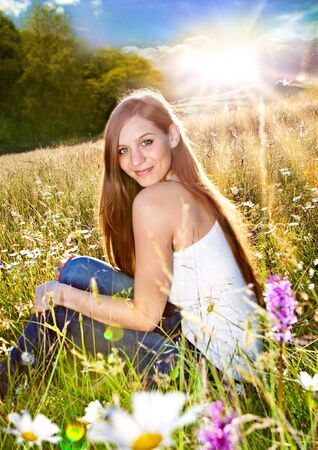 emotional freedom: beautiful young girl sitting in a marguerite meadow