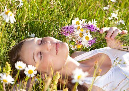 hermosa joven mentir en una pradera de Margarita  Foto de archivo