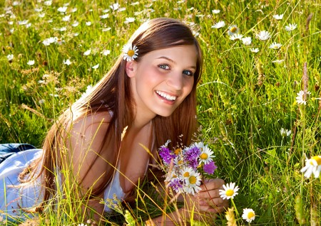 marguerite: beautiful young girl lying in a marguerite meadow