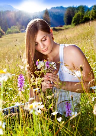 emotional freedom: beautiful young girl sitting in a sunset marguerite meadow