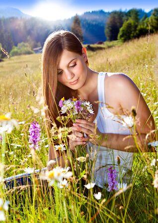 hermosa joven sentado en una pradera de la puesta del sol de Margarita