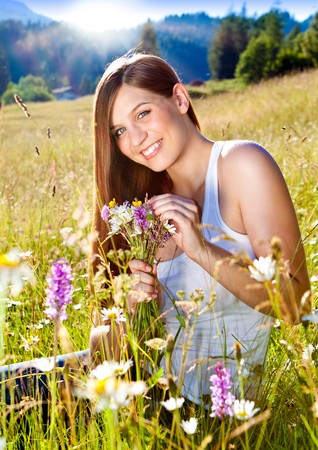 marguerite: beautiful young girl sitting in a sunset marguerite meadow
