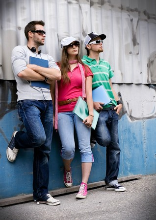 three students standing in front of a graffiti-wall photo
