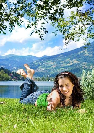lying in grass: bella joven disfrutando el verano