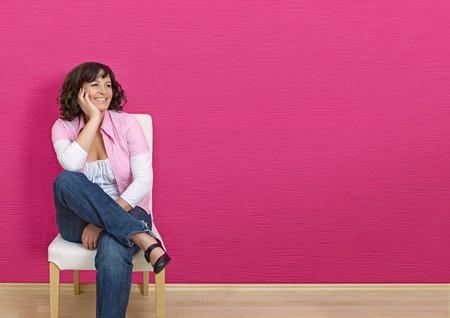 mani incrociate: donna seduta davanti a un muro rosa