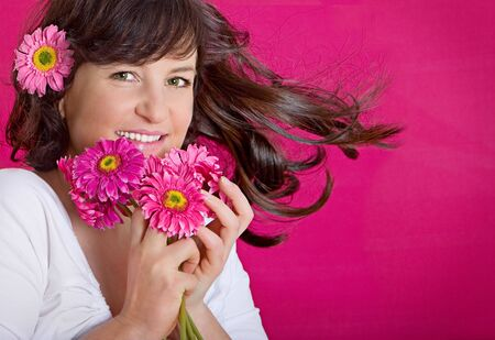 beautycare: young woman with pink flowers smiling into the camera