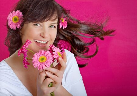 young woman with pink flowers smiling into the camera  photo