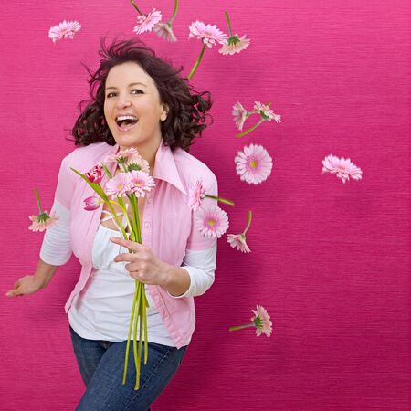 young woman standing in front of a pink wall and flying flowers photo