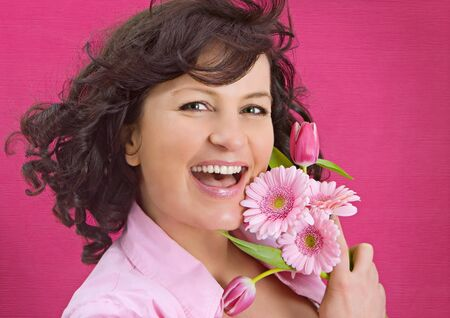 young woman with flowers in front of a pink wall photo