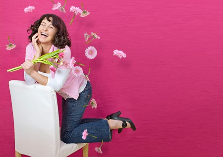 young woman in front of a pink wall on a chair with a lot of flying flowers Stock Photo