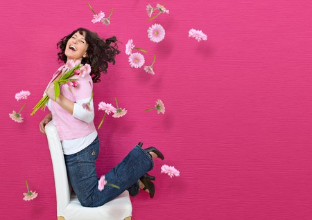 young woman in front of a pink wall on a chair with a lot of flying flowers  photo