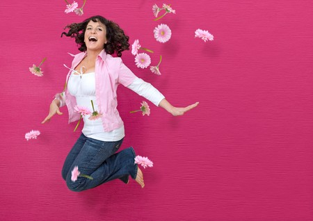 young woman in front of a pink wall jumping through flying flowers  Stock Photo